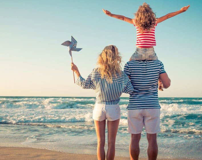Family of 3 with girl on fathers shoulders on St. George Island Beach