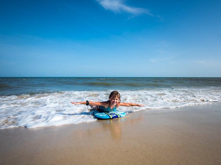 Little girl skim boarding on the beach