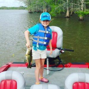 Small girl river fishing holding a small bass Apalachicola Florida