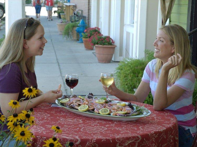 Two women enjoying shrimp and wine in Apalachicola