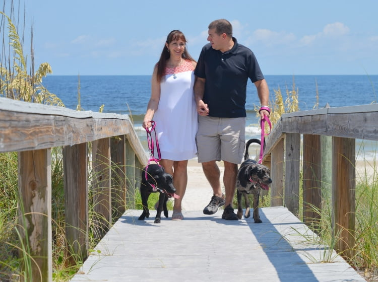 Couple walking their dogs on St. George Island