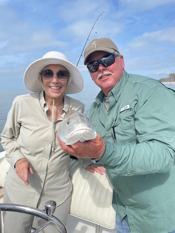 Couple on boat holding fish Apalachicola FL