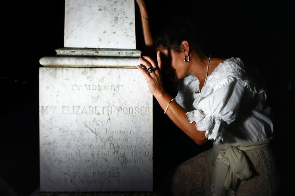 Photo of ghostly woman crying on a gravestone at the Chestnut Street Cemetery in Apalachicola, FL.
