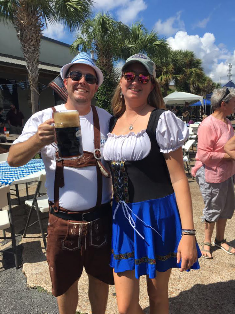 Photo of couple dressed in German clothing with beer at Oyster City Brewing Company's Oktoberfest in Apalachicola, FL.