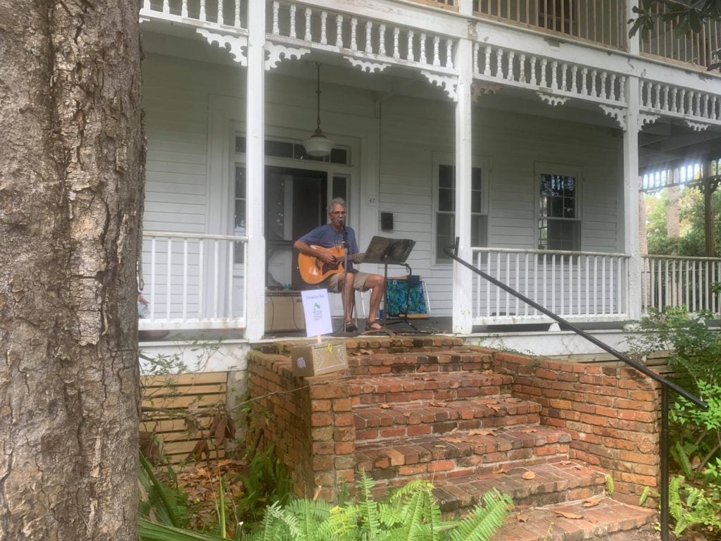 David Lloyd playing guitar and singing on a porch at Porch Fest in Apalachicola, FL.